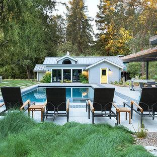 Diseño de casa de la piscina y piscina alargada, clásica renovada, rectangular, en patio trasero, con losas de hormigón