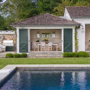 Medium sized rural back rectangular swimming pool in New York with a pool house.