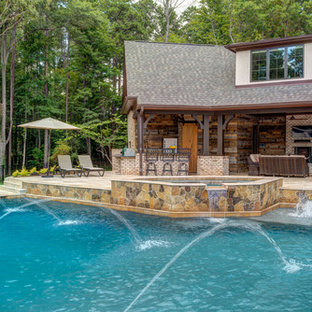 This is an example of a country backyard custom-shaped pool in Charlotte with a pool house.