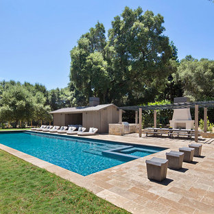 Photo of a large country backyard rectangular pool in San Francisco with a pool house and natural stone pavers.