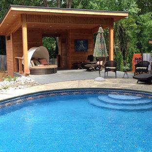Esempio di una piscina design rotonda dietro casa con una dépendance a bordo piscina e pavimentazioni in cemento