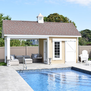 Mid-sized transitional backyard custom-shaped and concrete paver pool house photo in Boston