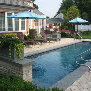 Imagen de piscina alargada, tradicional, rectangular, en patio trasero, con adoquines de piedra natural