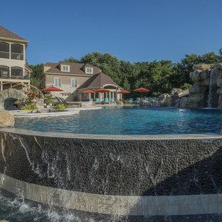 Foto de piscina con fuente infinita, extra grande, a medida, en patio trasero, con adoquines de piedra natural