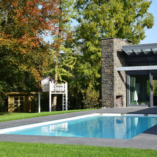 Imagen de piscina actual, de tamaño medio, rectangular, en patio trasero, con granito descompuesto