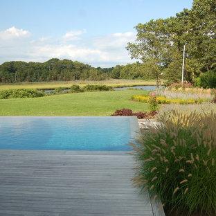 Diseño de piscina infinita, tradicional renovada, de tamaño medio, rectangular, en patio trasero, con entablado