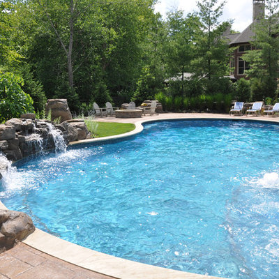 Example of a large mountain style backyard concrete paver and custom-shaped natural hot tub design in Cleveland
