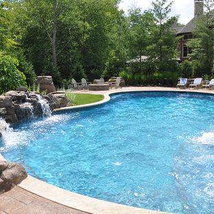Идея дизайна: большой естественный бассейн произвольной формы на заднем дворе в стиле рустика с джакузи и мощением тротуарной плиткой