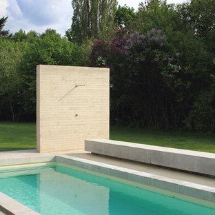 Idéer för stora funkis rektangulär träningspooler på baksidan av huset, med vattenrutschkana och marksten i betong