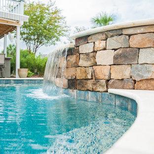 """Ispirazione per una grande piscina monocorsia tropicale a """"C"""" dietro casa con una vasca idromassaggio e pavimentazioni in pietra naturale"""