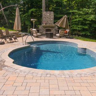 Modelo de piscina natural, tradicional, grande, a medida, en patio trasero, con adoquines de piedra natural