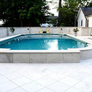 Imagen de piscina elevada, clásica, grande, a medida, en patio trasero, con suelo de hormigón estampado