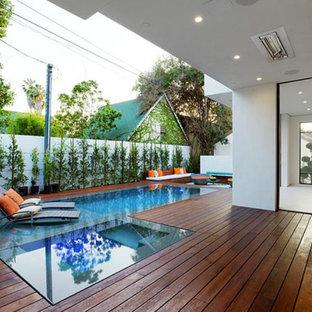 """Esempio di una piscina monocorsia moderna a """"L"""" di medie dimensioni e dietro casa con pedane"""