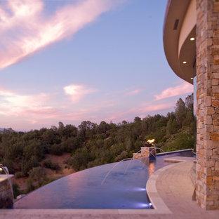 Bild på en mycket stor funkis anpassad infinitypool på baksidan av huset, med en fontän och marksten i betong