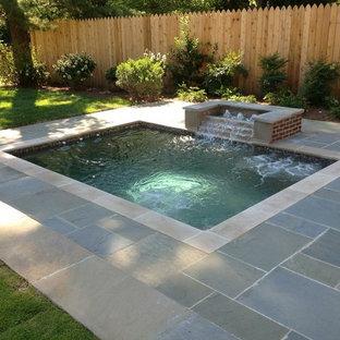 Ejemplo de piscinas y jacuzzis tradicionales, de tamaño medio, rectangulares, en patio trasero, con adoquines de piedra natural