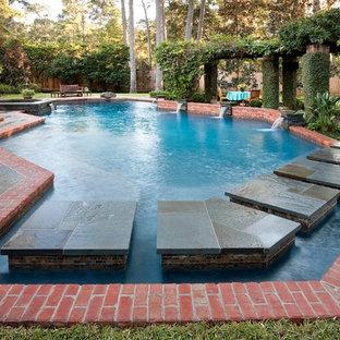 Diseño de piscina con fuente ecléctica, grande, a medida, en patio trasero, con adoquines de piedra natural