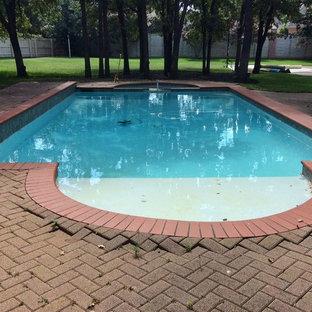 Ejemplo de piscina alargada, romántica, de tamaño medio, rectangular, en patio trasero, con adoquines de ladrillo