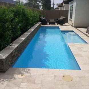 Ejemplo de piscina alargada, actual, de tamaño medio, rectangular, en patio trasero, con suelo de baldosas