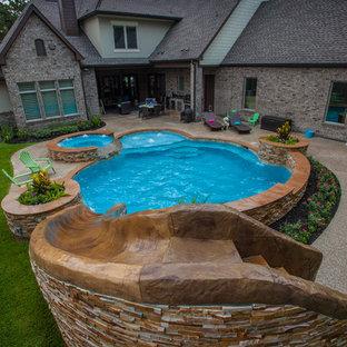 Aménagement d'une piscine sur une terrasse en bois naturelle et arrière moderne de taille moyenne et sur mesure avec un toboggan.