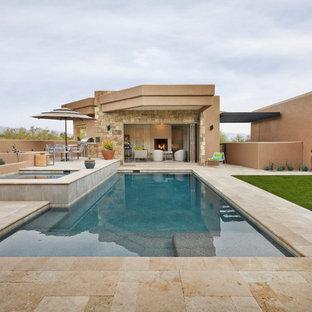 Ejemplo de casa de la piscina y piscina alargada, de estilo americano, rectangular, en patio trasero, con suelo de baldosas