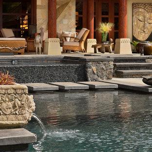 Ejemplo de piscina infinita, asiática, de tamaño medio, rectangular, con adoquines de piedra natural