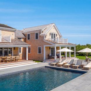 Modelo de piscina alargada, marinera, grande, rectangular, en patio trasero, con adoquines de hormigón
