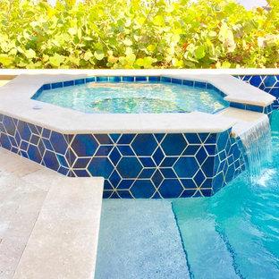 Immagine di una piscina monocorsia stile marino rettangolare di medie dimensioni e dietro casa con una vasca idromassaggio e pavimentazioni in pietra naturale