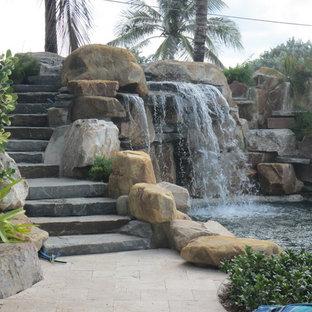 Diseño de piscina con fuente alargada, tropical, de tamaño medio, a medida, en patio trasero, con adoquines de piedra natural