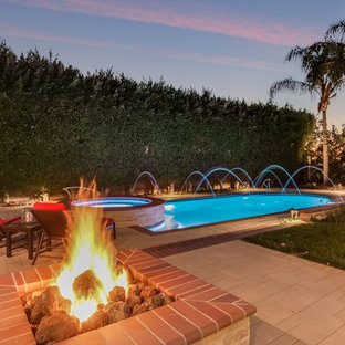Mid-sized transitional backyard brick and custom-shaped hot tub photo in Orange County