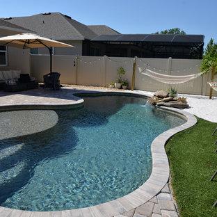 Foto de piscina costera, de tamaño medio, a medida, en patio trasero, con adoquines de ladrillo