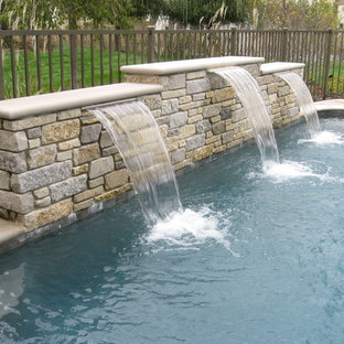 Example of a classic backyard stone and rectangular pool design in Chicago