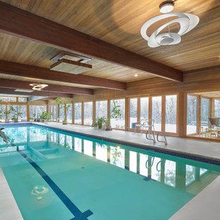 Ejemplo de piscina alargada, minimalista, extra grande, interior y rectangular, con losas de hormigón