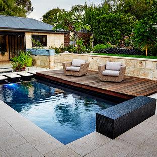Ispirazione per una piscina tropicale rettangolare in cortile con piastrelle