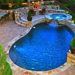 """Ispirazione per una grande piscina naturale design a """"C"""" dietro casa con una vasca idromassaggio e pavimentazioni in pietra naturale"""