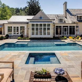 Неиссякаемый источник вдохновения для домашнего уюта: большой прямоугольный бассейн на заднем дворе в классическом стиле с покрытием из каменной брусчатки