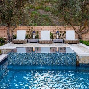 Foto de piscinas y jacuzzis alargados, contemporáneos, grandes, rectangulares, en patio trasero, con adoquines de piedra natural
