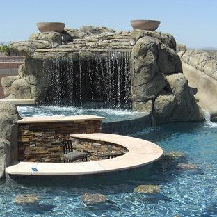 Idee per una grande piscina tradizionale personalizzata dietro casa con un acquascivolo e lastre di cemento