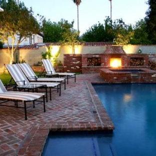 Modelo de piscinas y jacuzzis elevados, retro, en forma de L, en patio trasero, con adoquines de ladrillo