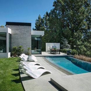 Idee per una piscina a sfioro infinito moderna personalizzata dietro casa con lastre di cemento