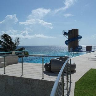 Immagine di una piscina a sfioro infinito tropicale personalizzata di medie dimensioni e dietro casa con un acquascivolo e lastre di cemento
