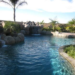 Ejemplo de piscina con fuente natural, moderna, de tamaño medio, a medida, en patio trasero, con granito descompuesto