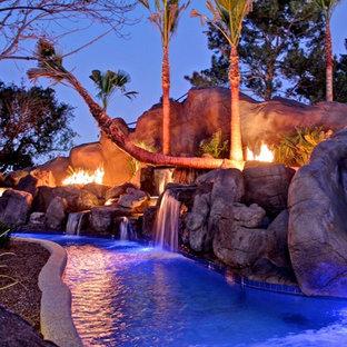 フェニックスの巨大なトロピカルスタイルのおしゃれな裏庭プール (タイル敷き) の写真