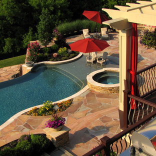 Photo of an expansive traditional backyard custom-shaped lap pool in New York with a hot tub and natural stone pavers.