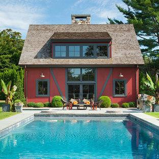 Ejemplo de casa de la piscina y piscina de estilo de casa de campo, rectangular, en patio trasero, con losas de hormigón