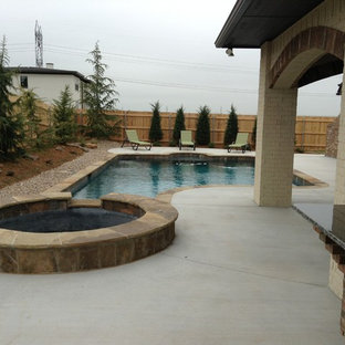 Design ideas for a small traditional backyard custom-shaped pool in Oklahoma City with a hot tub and concrete slab.
