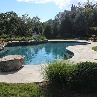 Modelo de piscina elevada, tradicional renovada, grande, tipo riñón, en patio trasero, con adoquines de piedra natural