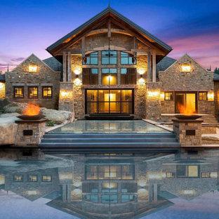 Diseño de piscina infinita, rural, grande, rectangular, en patio trasero, con adoquines de piedra natural