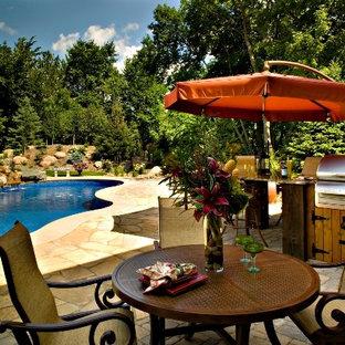 Foto de piscina con fuente nórdica, a medida, en patio trasero, con adoquines de ladrillo