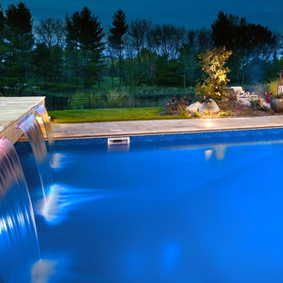 This is an example of a large scandinavian backyard rectangular pool in Minneapolis with a hot tub and natural stone pavers.