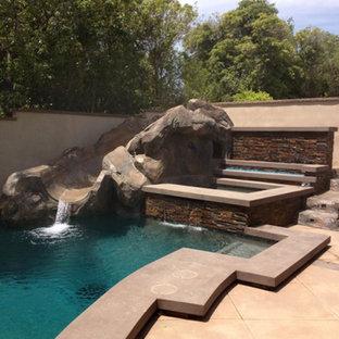 Foto di una grande piscina fuori terra tradizionale rettangolare dietro casa con un acquascivolo e piastrelle